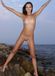 Young sexy brunette with puffy nipples nude on the rocks during the storm