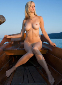 Nude blonde goddess Corinna is nude in the boat