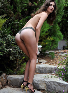 Tall sexy brunette strips in the garden